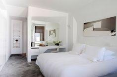 chambre blanche aménagée avec une coiffeuse blanche et moderne et un dressing blanc encastré dans le mur