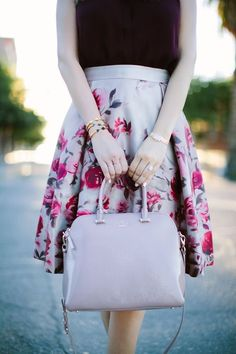 A modern take on mauve. This mauve purse is perfectly matched to the floral skirt, and the velvet blouse complements the colors of the blossoms, pulling the look together beautifully.