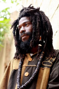 A young man with a full beard and thick dreadlocks, gazes calmly in thought.