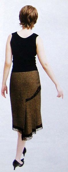 This a back view of a herringbone brown skirt that designed with asymmetrical pleats on the right side for free movements of a wearer. the hemline and a curved line where pleats attached, is decorated with black lace trim. A customer who wears the skirt as daywear is happy and gets compliments.  Her feedback is precious to me!:))