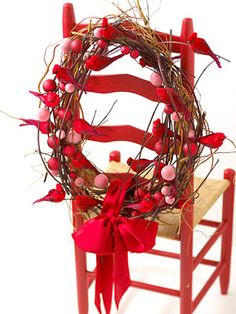 Natural Touch Wreath -  Handfuls of fresh curly willow branches and red dogwood provide a perch for cardinals and groupings of red-hue ornaments. A bright vintage ribbon droops gracefully at the bottom.