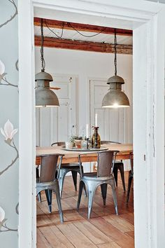 Perfect contrast between industrial kitchen dining area and the outer floral wallpaper