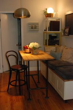 IKEA kitchen cupboard transformed into a dining room bench for extra storage. What a great idea in this NYC studio apartment!