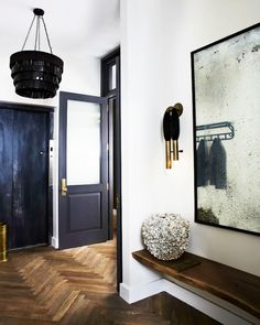 Black and wood details mingle in this small entryway in New York. Statement light fixtures demand attention and set the tone for the industrial yet chic design of the home.