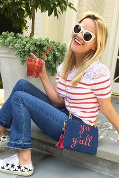 Reese Witherspoon wearing Saint Laurent Court Classic Star-Appliqued Leather Sneakers, Draper James Tailgate Tee, Draper James Crop Flare Fringe Denim, Draper James Denim Go Y'All Clutch in Crimson Grey, Draper James Pom Pom Fob in Blue Red and Draper James Cheers-Y-All Tumbler Set -and Pitcher