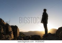 Girl watching sunset at the top of the mountain. Horizontal