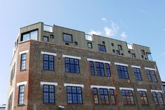 An IMAR cladding of corrugated perforated aluminium with an anodized gold finish crowns the renovation work of an old warehouse in the modern district of Whitec. Metal Facade, Perforated Metal, Corrugated Metal, Refurbishment, Exposed Brick, East London, Luxury Apartments, Facades, Metal Walls