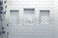 Shower: white subway tiles, gray grout, arabesque tile in the shampoo niches