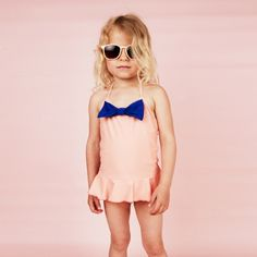 Cool Mini Rodini girl in a pink bathing suit and shades.