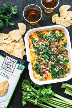 A traditional buffalo chicken dip recipe topped with bacon, scallions and parsley. Paired with Food Should Taste Good Lime Tortilla Chips + IPA beer.