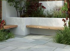 Contemporary hardwood benches built into a white rendered, walled seating/patio area Stonemarket: Garden range: Natural Stone: Trustone Fellstyle