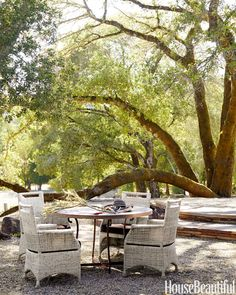 Oak trees shade a round table surrounded by wicker chairs — a favorite breakfast spot in a Sonoma, California, house designed by Rela Gleason.