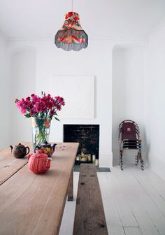 Love the painted floors, picnic table and all white including fireplace - with just a few pops of color