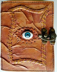 An attractive, embossed stitched, sacred eye journal with a binding wrap that overlaps under its front cover, with single metal bronze colored latch, for keeping its pages safe. Angled stitching around all outside edges, as well as the outside eye shape of its All Knowing Eye upon front center, surrounded by patterned stitch. The back cover and spine are interestingly tanned giving the appearance of a wood leathered wood grain. 120 heavy wt pages.