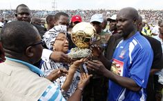 Former football player and Liberia's main opposition leader George Weah presents his Ballon D'or trophy to Liberia's President Ellen Johnson Sirleaf...