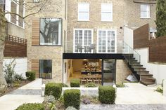 On the ground floor is an open-plan living room with French doors that open out onto a new terrace, which is built atop the kitchen extension with stairs leading down to the garden. On warm days, the wall of sliding doors off the kitchen will be left completely open, merging the inside and outside spaces.