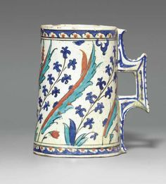 AN IZNIK POTTERY TANKARD  OTTOMAN TURKEY, CIRCA 1590  Of tapering cylindrical form with angular handle, the white body decorated in cobalt-blue, bole-red, turquoise and black outline with alternating large saz leaves and blue hyacinths curving to the left, the base and mouth with a narrow band of white and red half-rosettes on blue ground,   7¼in. (18.6cm.) diam.:
