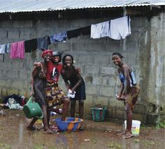 """""""Young ladies at the My Brother's Keeper Orphanage outside of Monrovia, Liberia, West Africa ,enjoy the rain while washing their clothes.""""  Carl Motsenbocker"""