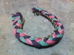 Pulsera de cadena con tejido en hilos color rosa, verde y morado.
