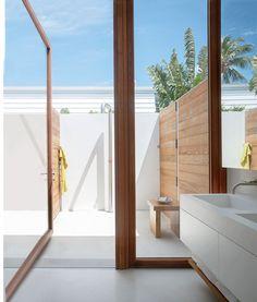 Em Kelly Klein Palm Beach, Florida, banheiro principal, que foi projetado por David Piscuskas da empresa 1100 Architect, a pia dupla é de Corian;  as portas de vidro com moldura de teca levar a um chuveiro ao ar livre.