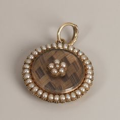 Seed pearl mourning pendant, the woven hair backing with overlaid seed pearl cluster and seed pearl outer edging also hair panel to reverse.