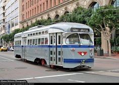On a typically overcast San Francisco morning, MUNI car 1070 heads east along Steuart Street near the Ferry Building. This PCC streetcar, built by the St. Louis Car Co. in 1946, is painted in the 1950s livery it once wore for New Jersey Transit in Newark, including the unique red wheels nicknamed 'Ruby Slippers'. Southern Pacific's former corporate headquarters on #1 Market Street looms in the background.