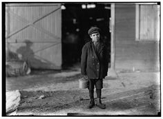 "Monongah Glass Co., Fairmont, W. Va. Jo Before a glass wks boy going home, 5 P.M. He says he is 12 years old, and has been at it one year: is a ""ketchin-up-boy"" $.70 a day: says glass business is all right. Asked if he was going to be a glassblower when he grows up, he said ""Sure!"" (See 185) Goes to school during school term: asked is [sic] he had to, he answered ""Don't unless I want to"" asked why he went then, said ""Want to learns something."" 1908.  Location: Fairmont, West Virginia."