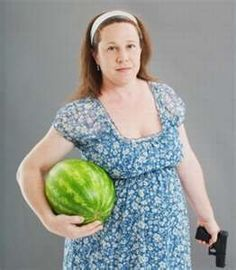 not sure what is funnier, the watermelon, the gun or the dress.