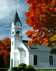 New England church with clock in the steeple is set off by autumn leaves