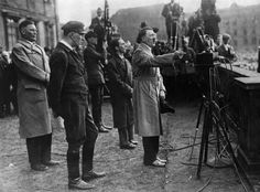 """Goebbels stands behind Hilter during a speech. One of the Nazis' major accomplishments was draining support away from the left-wing parties by addressing their rhetoric toward the struggling working class and championing a Marxism-free """"socialism of action"""" marked by hot soup and solidarity. Goebbels promised the """"right to work"""" and """"a socialist Germany that gives bread to its children once again."""""""
