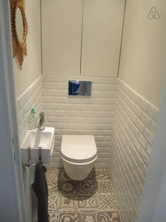 Tiny white brick tiled  toilet modern wall hung very clean modern smile I lke for guest toilet
