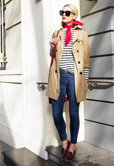 Tan coat, striped shirt, blue jeans, loafers, red bag, red bandana neck scarf, and sunglasses