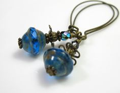 https://flic.kr/p/am5b9R | Sapphire Czech Glass Vintage Style Earrings | 10x11 Firepolished Czech Glass Flying Saucer beads in sapphire with a Picasso finish. The tops and bottoms of the beads feature an opaque sandy Picasso finish and the middle band is in clear, gemstone cut sapphire. Paired with 4mm antiqued brass melon beads and 4mm faceted sapphire AB finish Czech glass rounds. Earrings dangle a dramatic 2.75 inches (69.85mm)