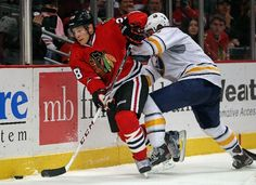 CHICAGO, IL - OCTOBER 12: Ben Smith #28 of the Chicago Blackhawks controls the puck under pressure from Mark Pysyk #3 of the Buffalo Sabres at the United Center on October 12, 2013 in Chicago, Illinois. The Blackhawks defeated the Sabres 2-1. (Photo by Jonathan Daniel/Getty Images)