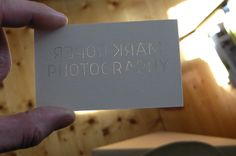 inverted see through letters on a photograph's business card, by salmon, brillant