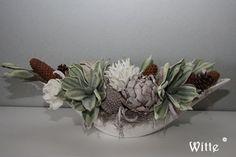 Groene, witte en bruine foambloemen gecombineerd met natuurlijke producten in een witte vloot. mooi voor op een schouw, dressoir of kastje