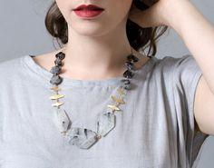 A brass and quartz necklace makes a modern statement.