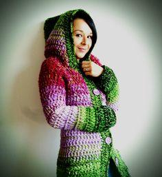 Rozkvitnutá lúka (sveter) Dlhý, ručne háčkovaný sveter s veľkou kapucňou a dvoma vreckami. Sveter je vytvorený kombinovaním pletacích priadzí, ladený v zeleno-ružových farbách. Je hrubý, teplý, vhodný aj ako kabát na prechodné obdobia. Materiál: 100% akryl. Veľkosť: 36/38