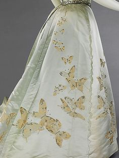 """1898 House of Worth """"This gown is made from a very special fabric which was woven à la disposition to fit the shape and dimensions of the skirt so that the butterflies flutter upward from the hem and, being graduated in size, seem to disappear in the distance. """""""