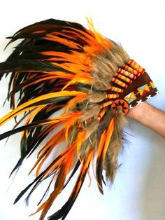 For Children: Indian Sunset Feather Headdress Fun and Original Costume for children, long rooster orange feathers all around. Is a hat, whith rubber adjustable band . From 7 to 14 years old. Circumference: 21 inch. Let your kid be and Indian and make the greatest photoshoot ever! **This product will be ship with INTERNATIONAL EMS EXPRESS : 5-10 days** ( Also available to send express in 3-4 days worldwide with extra fee, ask for it)