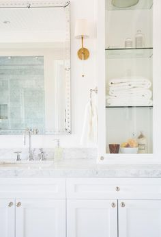 White and gray bathroom features a white shaker vanity topped with carrera marble under a studded ...