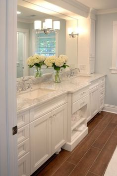 Love the white cabinetry, the wood tile, and the large mirror. The countertop is beautiful.