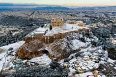 An exceptional aerial view of the snow-covered citadel, the Acropolis of Athens, which includes the celebrated Parthenon.