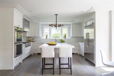 Well appointed white u-shaped kitchen is lit by an Arteriors Jalen Chandelier hung over a white center island topped with a white marble countertop seating two slipcovered barstools on a gray wash wood floor.