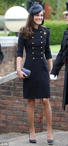 Well heeled: Kate wore a navy military-style dress believed to be Burberry Prorsum with a matching fascinator. She adorned her dress with a gold shamrock brooch loaned to her from the regiment