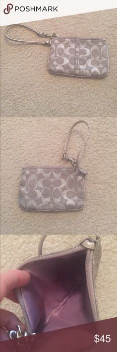 Silver Coach Wristlet Used Used silver  Coach wristlet. Worn, but still has a lot of life left! Some makeup stains on the inside (see picture). Could be washed out with right products. Coach Accessories
