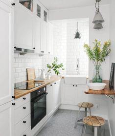 modele de cuisine blanche équipée avec meuble haut et meuble bas blanc, plan de travail bois, credence et mur carrelage blanc