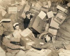 US military personnel surrounded by parcels in a World War II holiday mail rush do their best to handle the mountain of boxes and sacks of mail. In the effort to get this mail overseas on time and in.