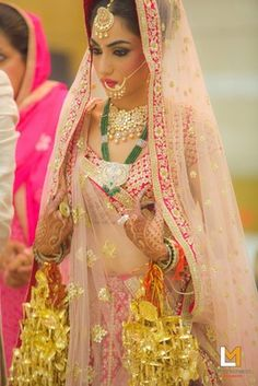 Indian Wedding Jewelry - The bride is wearing a gorgeous pastel pink and plum coloured lehenga with gold kaleere, gold polki bridal necklace, gold nosering, maangtikka and green emerald raani haar | WedMeGood #wedmegood #bride #bridal #portraits