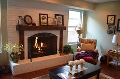 """I went from an ugly fireplace to this, with a custom-made rough-hewned timber mantle. I swore I would never paint over brick, but this...this turned out fantastic! Click through to see the """"before,"""" the process, and the """"after."""" #fireplace #mantle #remodel #makeover"""